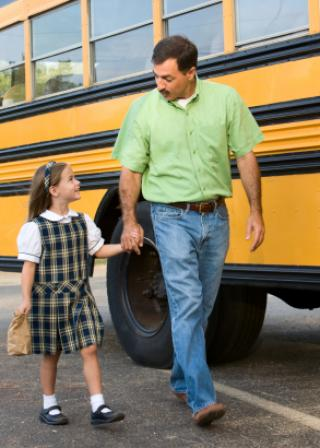 Dad and daughter walking next to school bus